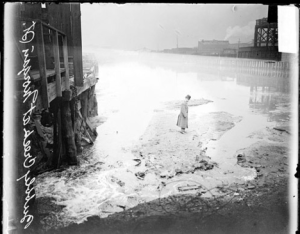 A man stands upon waste on Bubbly Creek, 1911.  Chicago Daily News.
