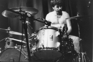 Michael Dahlquist, shirtless and hammering away at his drums.